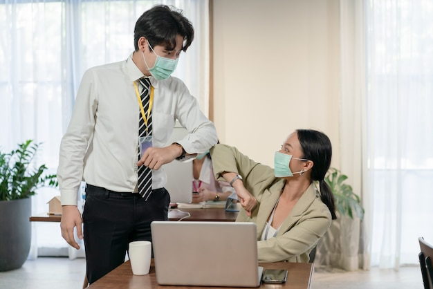 Young asian colleagues male and female wearing mask greeting with bumping elbows during coronavirus covid-19 epidemic in office