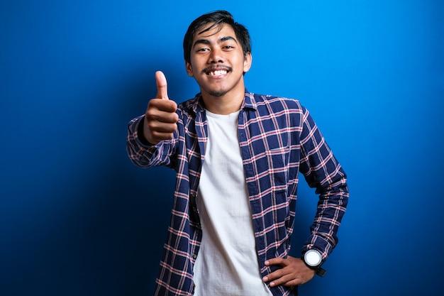 Okサインで笑っている若いアジアの大学生。大丈夫サインをやって青い背景の上の幸せなアジアの学生。