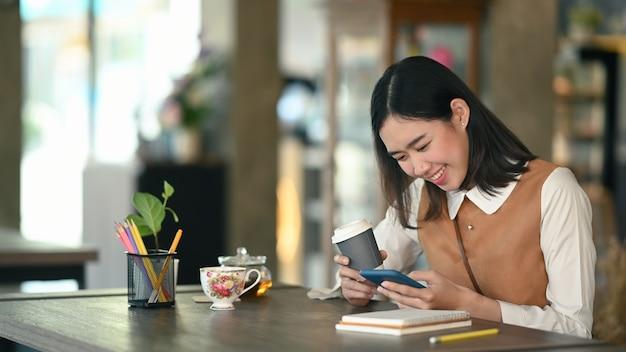 Молодая азиатская женщина студента колледжа ослабляя в кофейне и используя умный телефон