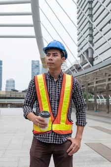 Young asian constructor with safety helmet in work vest holding coffee cup in construction site