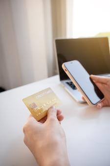 Молодая азиатская женщина-потребитель рука держит кредитную карту и смартфон для покупок в интернете