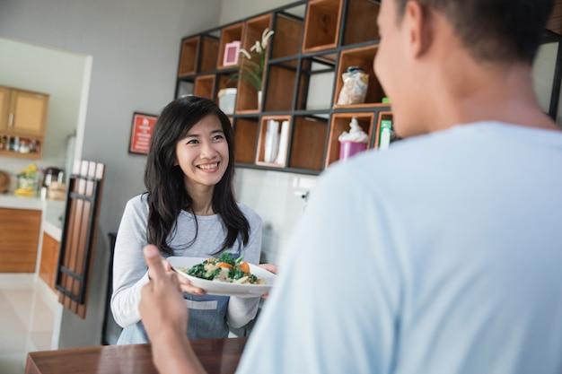 キッチン調理で若いアジアのカップル