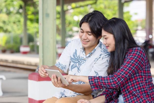 駅で目的地の旅行を見つけるためにタブレットを使用して若いアジアのカップルのバックパッカー