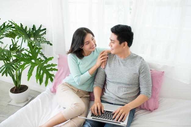 젊은 아시아 커플 집에서 인터넷 검색, 노트북 사용 및 미소