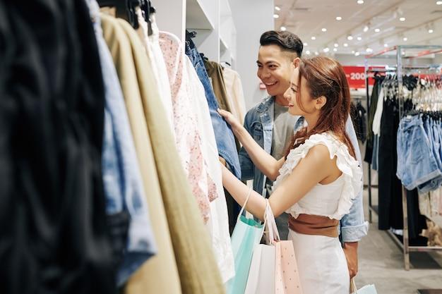 쇼핑몰에서 옷을 선택하는 젊은 아시아 부부