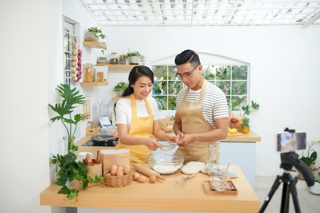 Молодая азиатская пара готовит вместе и записывает живое видео для видеоблога и социальных сетей с профессиональной камерой