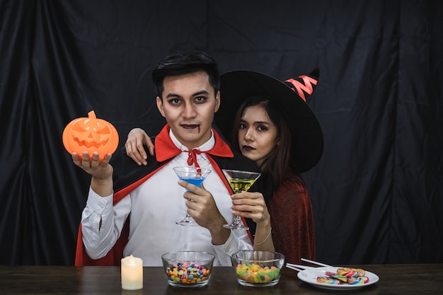 Young asian couple in costume witch and dracula with celebrate halloween party for clink glass and drink in halloween festival. couple in costume celebrate halloween party black cloth background.
