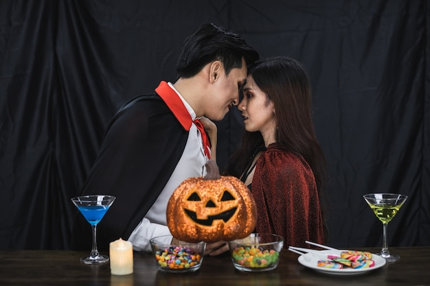 Young asian couple in costume witch and dracula with kissed in celebrate party halloween festival. couple in costume celebrate halloween party black cloth background.