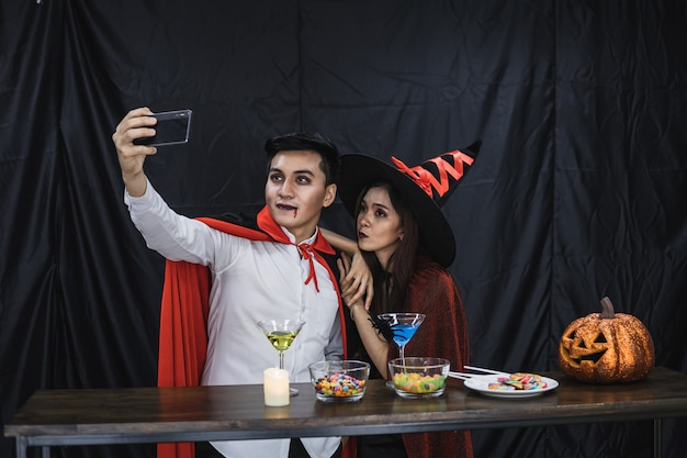 Young asian couple in costume witch and dracula with selfie by mobile in celebrate party halloween festival. couple in costume celebrate halloween party black cloth background.