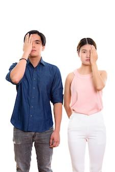 Young asian couple covering face together isolated