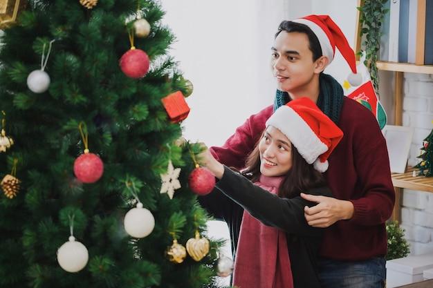 젊은 아시아 부부는 크리스마스 트리를 장식하고 가정 배경에서 크리스마스 트리를 장식하고 새해 복 많이 받으세요. 연인 개념의 크리스마스 축하입니다.