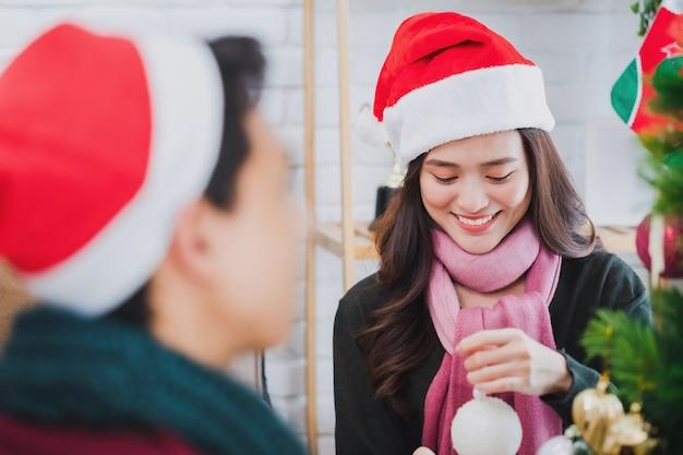 クリスマスにクリスマスツリーを飾る若いアジアのカップル