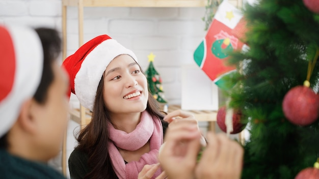 Young asian couple decorating a christmas tree