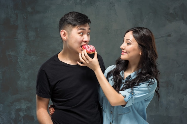 若いアジアのカップルは、灰色のスタジオの背景に甘いカラフルなドーナツを食べることを楽しむ