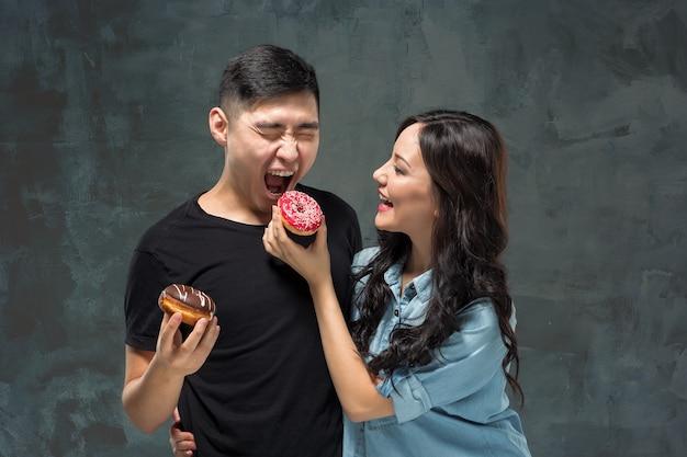 若いアジアのカップルは灰色のスタジオで甘いカラフルなドーナツを食べることを楽しむ