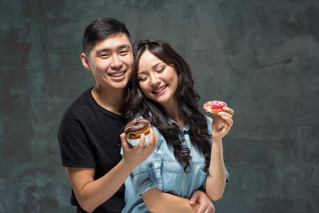 젊은 아시아 몇 달콤한 다채로운 도넛의 식사를 즐길 수