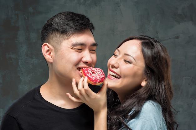 Молодые азиатские пары наслаждаются едой сладкого красочного пончика