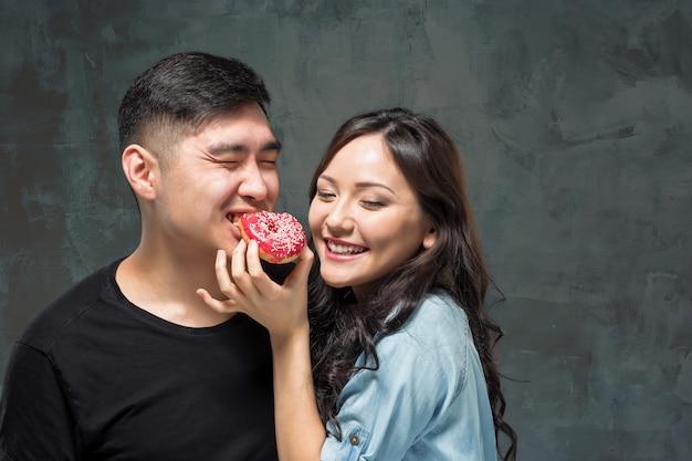 若いアジアのカップルは甘いカラフルなドーナツを食べることを楽しむ