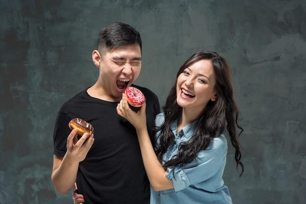 Молодая азиатская пара любит есть сладкий красочный пончик