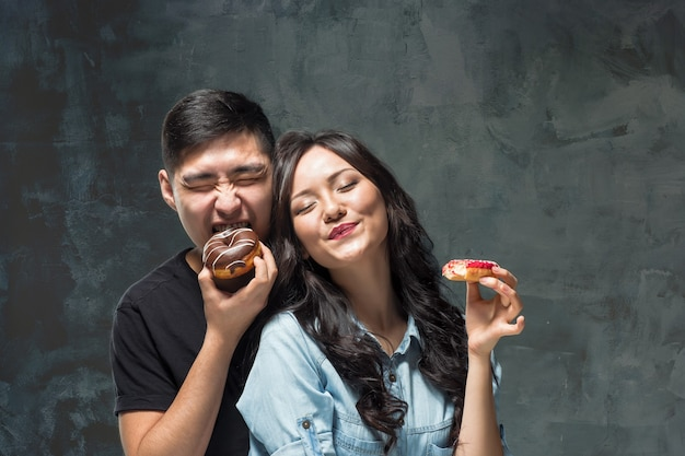Young asian couple enjoy eating of sweet colorful donut on gray studio background