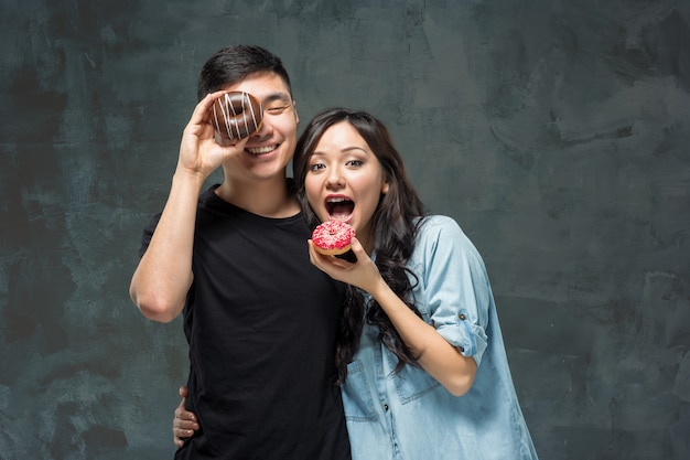 Young asian couple enjoy eating of sweet colorful donut