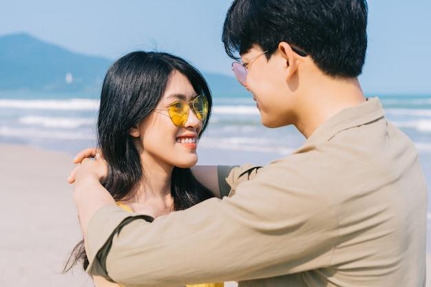 해변에서 여름 휴가 즐기는 젊은 아시아 부부