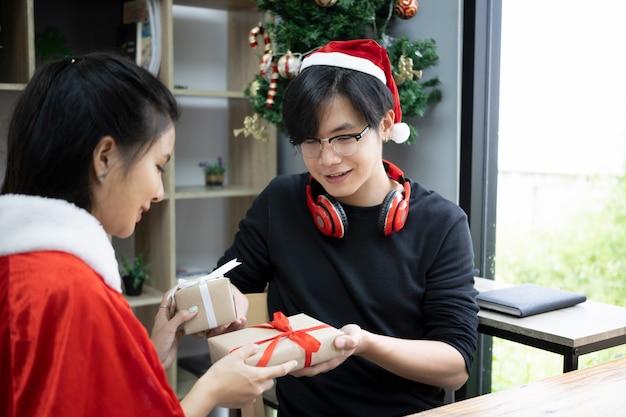 젊은 아시아 부부는 집에서 함께 크리스마스를 축하하면서 선물을 교환합니다.