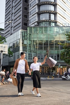 Young asian couple going out for shopping on le loi road in hochiminh city, vietnam
