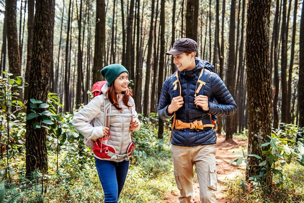 Young asian couple hikers with backpack walking