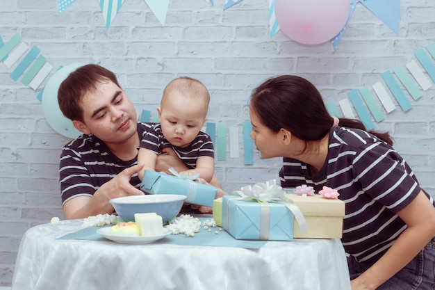 Young asian couple holding cute toddle child boy with love feeding milk cup playing cheerful in birthday celebrating, lifestyle beautiful mother, father have fun hold son kiss taking care at room home