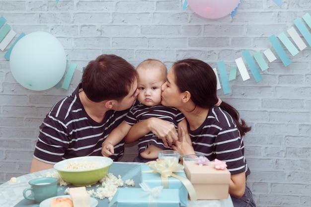 若いアジアカップル持株かわいいよだれを抱いて愛情を込めてミルクカップを食べて陽気に遊んで誕生日を祝う、ライフスタイルの美しい母、父は楽しい家で息子のキスを保持