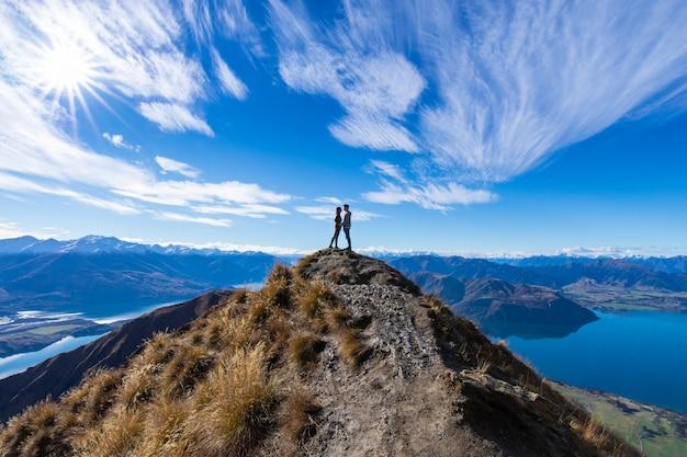 Young asian couple holding hands kissing at roy's peak lake wanaka new zealand
