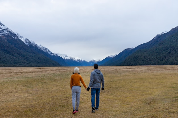 Young asian couple holding hands walking into mountain eglinton valley fiordland national park new zealand