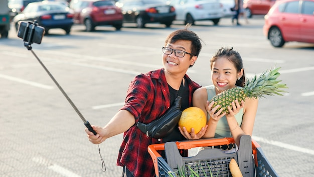 Young asian couple holding in their hands pineapple and melon and making selfie photo.