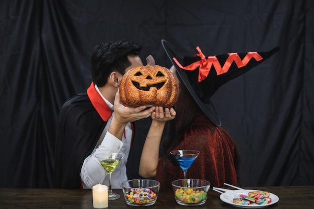 ハロウィーンパーティーを祝い、顔を覆うカボチャとキスした衣装の魔女とドラキュラの若いアジアのカップル。衣装を着たカップルは、ハロウィーンパーティーの黒い布の背景を祝います。