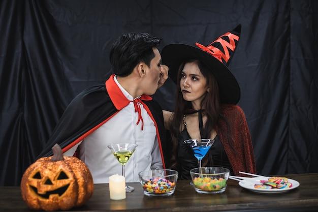 コスチューム魔女とドラキュラの若いアジアのカップルは、ハロウィーンフェスティバルでチャリンという音と飲み物のためのハロウィーンパーティーを祝います。衣装を着たカップルは、ハロウィーンパーティーの黒い布の背景を祝います。