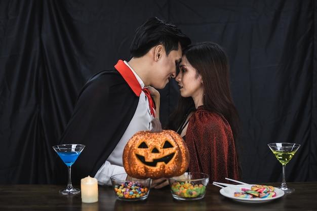 コスチューム魔女とドラキュラの若いアジアのカップルがパーティーハロウィーンフェスティバルでキスをしました。衣装を着たカップルは、ハロウィーンパーティーの黒い布の背景を祝います。