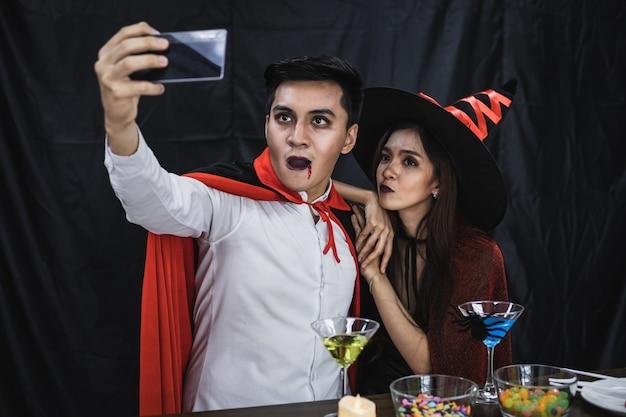 パーティーハロウィーンフェスティバルを祝うモバイルでselfieと衣装の魔女とドラキュラの若いアジアのカップル。衣装を着たカップルは、ハロウィーンパーティーの黒い布の背景を祝います。