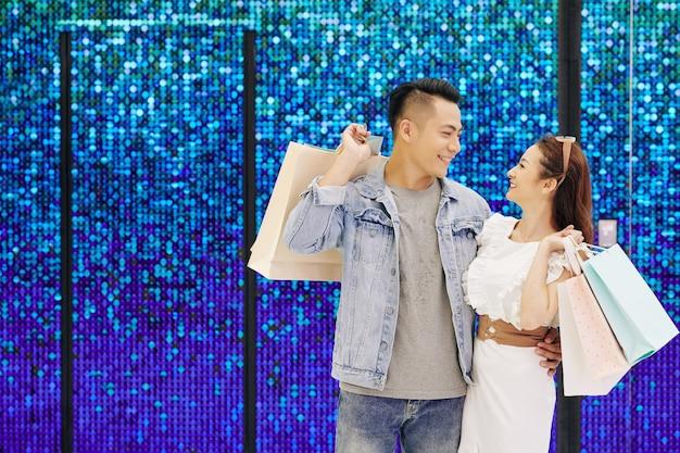 Молодая азиатская влюбленная пара стоит у сверкающей стены с хозяйственными сумками и смотрит друг на друга