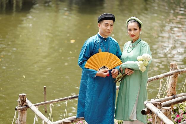 연꽃과 종이 부채가 있는 연못에 서서 카메라를 바라보는 전통 의상을 입은 젊은 아시아 부부