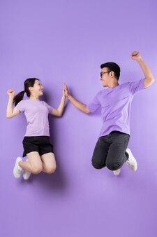 보라색 배경에 점프하는 젊은 아시아 커플