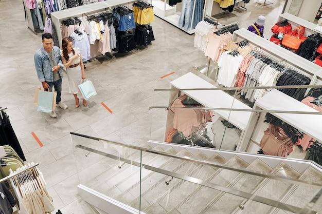 젊은 아시아 부부는 어디로 가야할지 결정하고 다른 방향으로 가리키는 큰 옷가게에서 길을 잃었습니다.