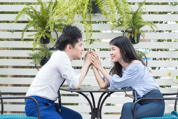 Young asian couple in love smiling in garden, happy mixed race teenager concept