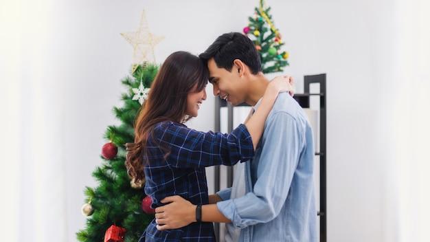 Молодой азиатский любовник пары танцует вместе на фестивале праздника рождества и нового года у себя дома.