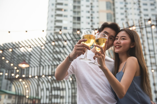 Young asian couple lover have fun dancing and drinking in night party on rooftop floor nightclub hand holding beer bottle and eye contact flirting at couple party.focus on two glasses of wine.