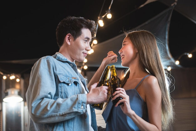 Young asian couple lover have fun dancing and drinking in night party on rooftop floor nightclub hand holding beer bottle and eye contact flirting at couple party.