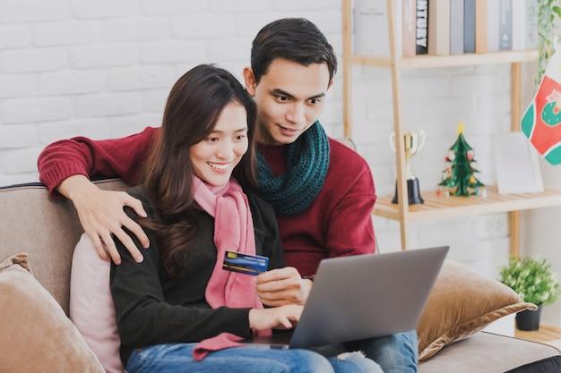 装飾された部屋でクレジットカードとラップトップでオンラインショッピングをする若いアジア人カップル