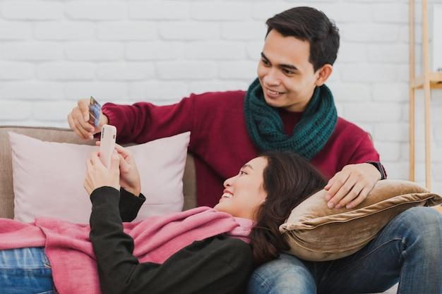 Молодой азиатский любовник пара делает покупки онлайн с помощью кредитной карты и смартфона в комнате, украшенной рождественскими елками на домашнем фоне. концепция празднования рождества.