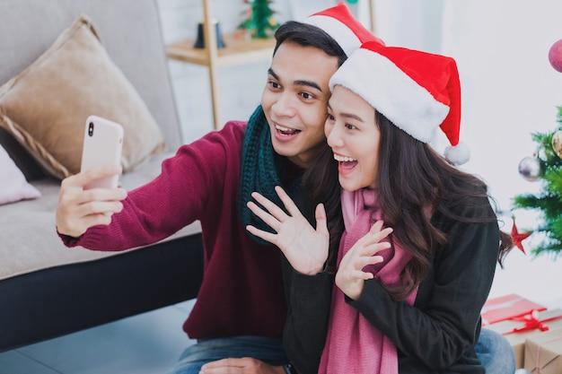 サンタクロースの帽子をかぶっている若いアジアのカップルの恋人。
