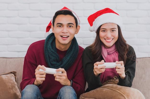 Молодой азиатский любовник пары в шляпе санта-клауса.